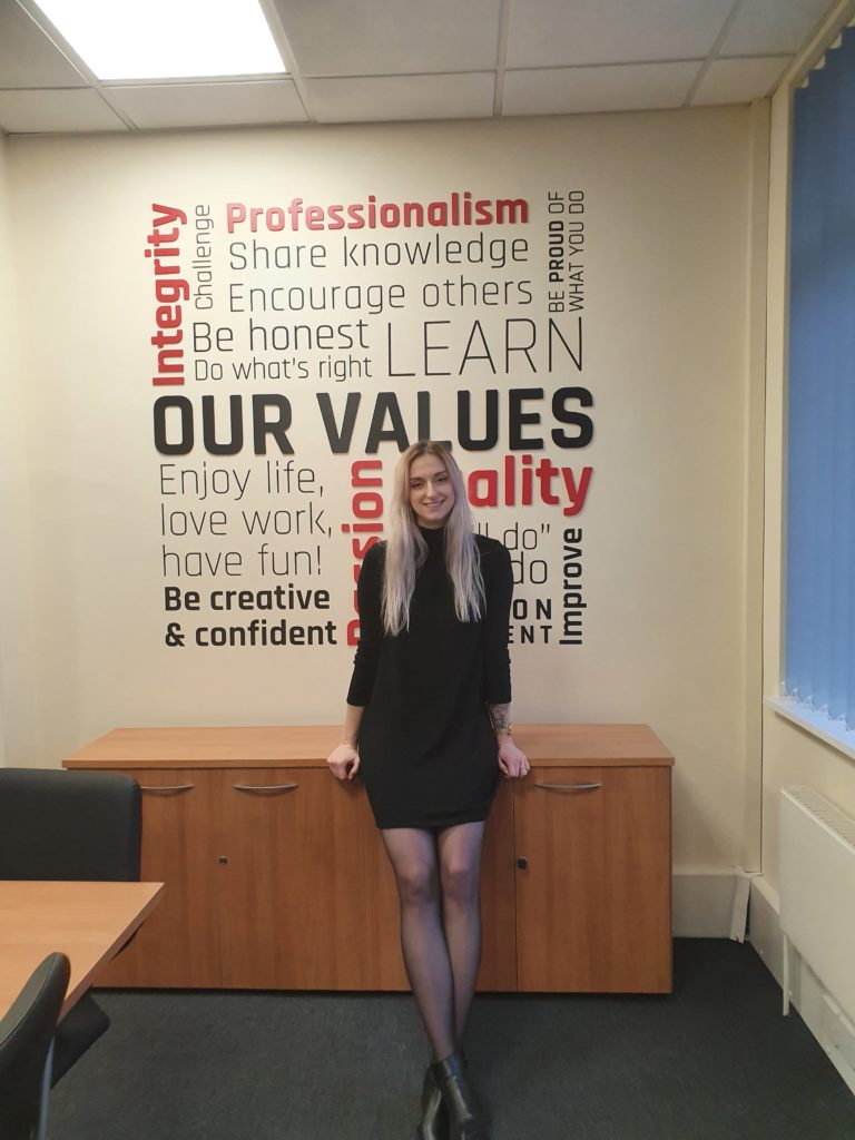 Senior Researcher Emily Damerell pictured in front of SafeLane company values