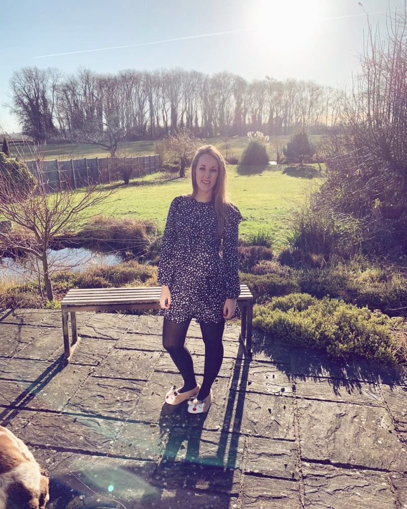 Charlotte Haines Staff Spotlight feature photograph. Charlotte stands on decking in a beautiful garden on a winter's day.